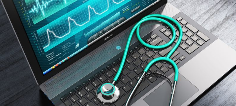 laptop with a stethescope sitting on the keyboard