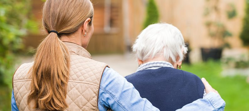 young woman walking away with arm around elderly woman's shoulders