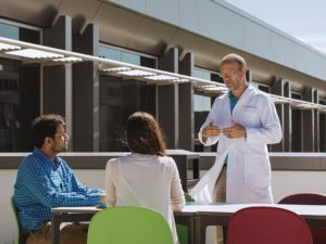 Doctor Noll Campbell talking with Regenstrief staff members on the roof