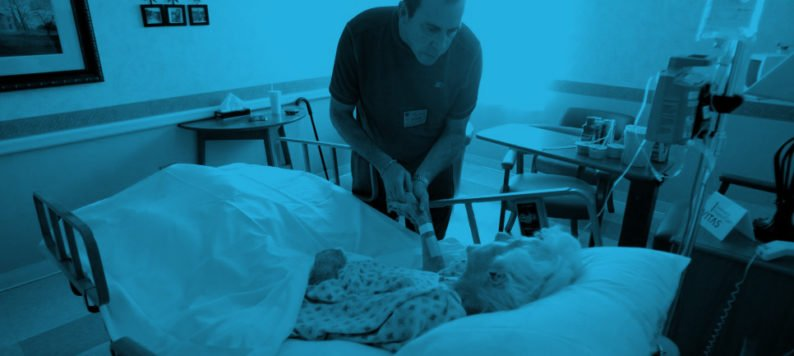 Photo of a male doctor taking the hand of an elderly woman in a hospital bed
