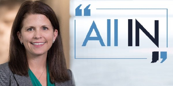 Kathleen Unroe next to All IN logo