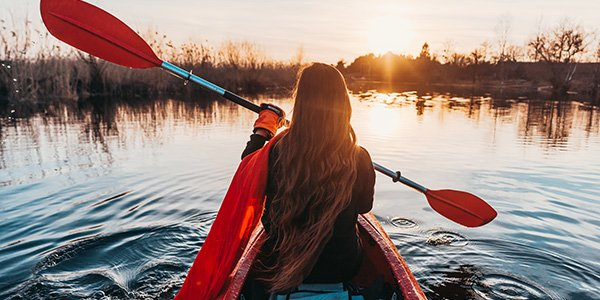 Back view of girl holding paddle in a kayak