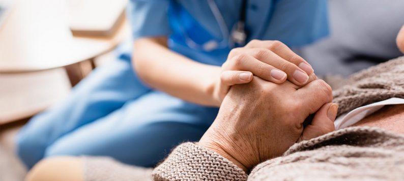 Nurse holding older person's hand.