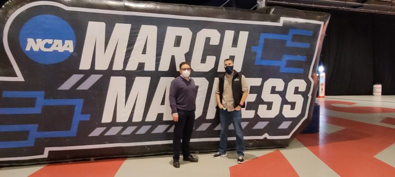 Dr. Peter Embi and Dr. Joshua Vest in front of March Madness sign