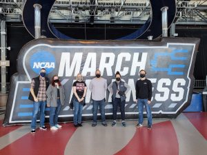Research team in from of March Madness sign all wearing masks